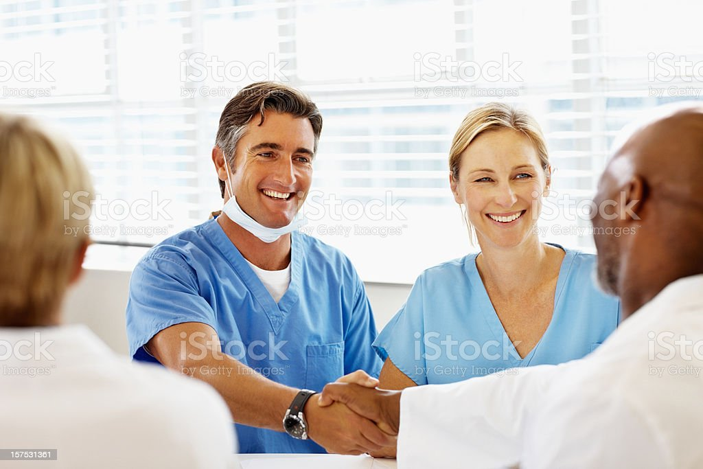 Male doctors shaking hands in hospital royalty-free stock photo