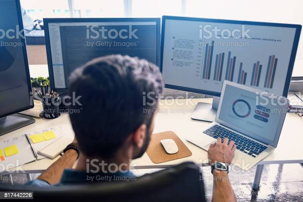 Man creating statistics in modern office. He working on digital devices while sitting at table and turning back to camera