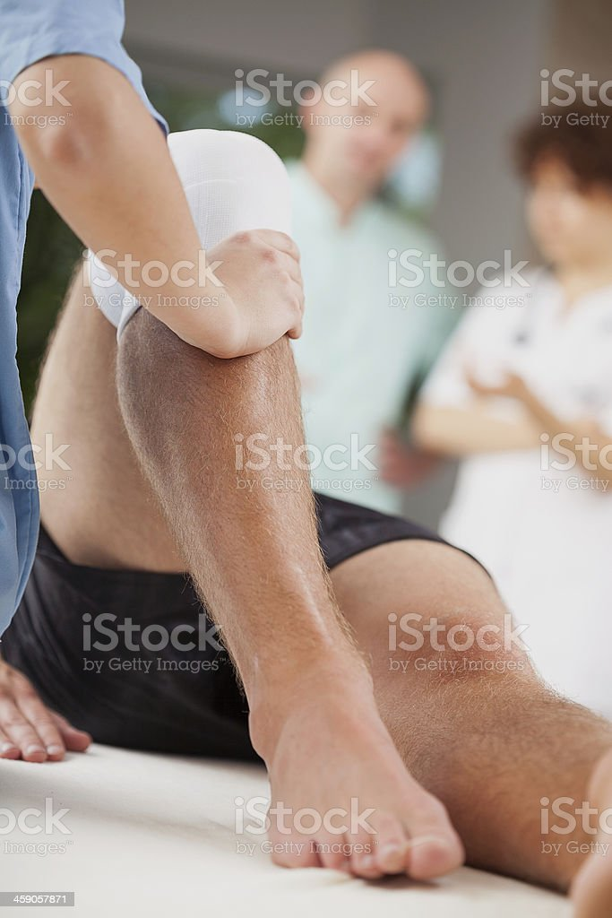 Male doing leg rehabilitation with people behind him stock photo