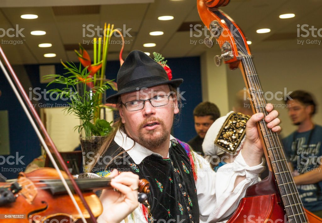male double bass player in traditional Slovenian costume performing in live show indoors stock photo
