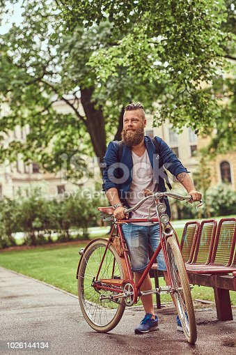 istock Male dressed in casual clothes, walking with a retro bicycle in a city park. 1026144134