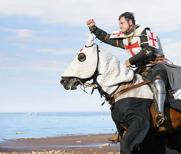 male dressed in king templar outfit while riding a horse - knight on horse stock photos and pictures