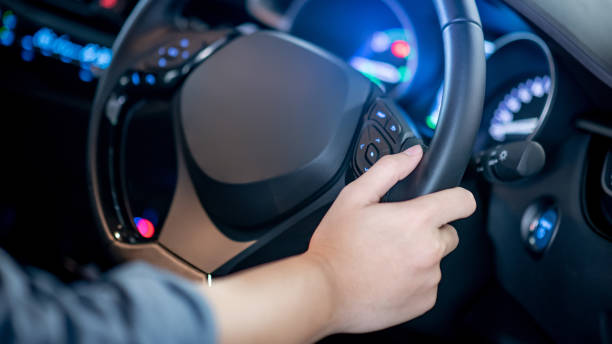 Male driver holding steering wheel in modern car with blue light dashboard on the console. Auto transport technology for automobile industry concept stock photo
