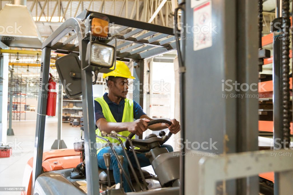 Male driver looking away while driving forklift Male driver looking away while driving forklift. Serious engineer is working in manufacturing company. He is in distribution warehouse. 25-29 Years Stock Photo