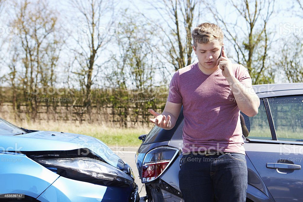 Male driver making a phone call after a car accident stock photo