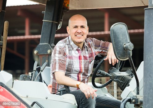 istock male driver operating modern tractor 594079060