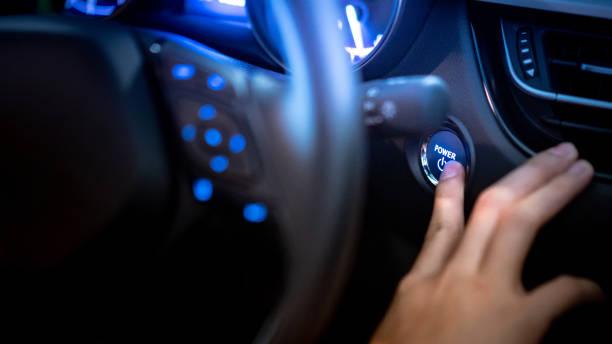 manliga förare att skjuta bilmotor start-stopp knappen eller power tändning av ratten i modern bil med blå ljus dashboard på konsolen. automatisk transportteknik för bilindustrin - hand tänder ett ljus bildbanksfoton och bilder