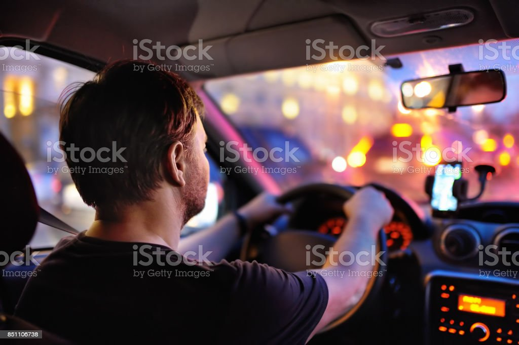 Male driver ride a car during evening traffic jam stock photo