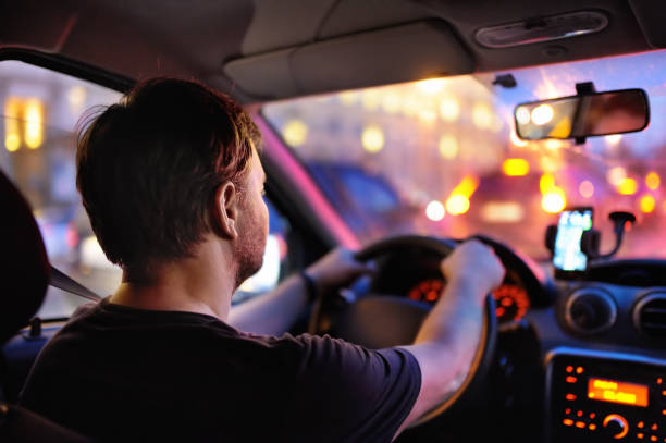 Male driver ride a car during evening traffic jam Male driver ride a car during evening traffic jam. Drive in the night city. Inside view. traffic jam stock pictures, royalty-free photos & images