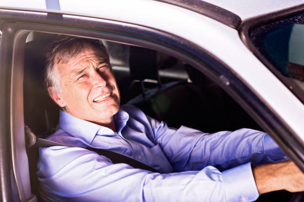 Male driver squinting into bright sunlight through car window A middle-aged man driving his car squints as he looks through his open window into very bright sunlight. dazzled stock pictures, royalty-free photos & images