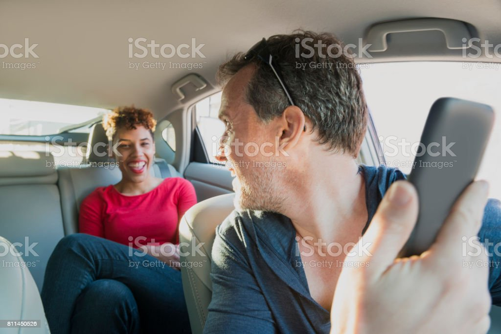 Male Driver with Mobile Phone Greets Happy Smiling Passenger Miami stock photo