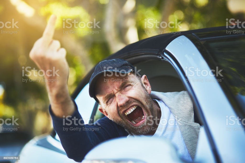 Male driver yells, giving rude middle-finger gesture through car window stock photo