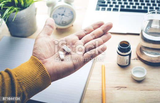 istock Male eating medicine,pill (vitamin) on work in morning. 871644134