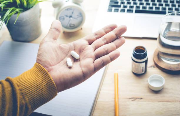 tıp, ilaç (vitamin) çalışma sabah yemek erkek. - ağrı kesici stok fotoğraflar ve resimler