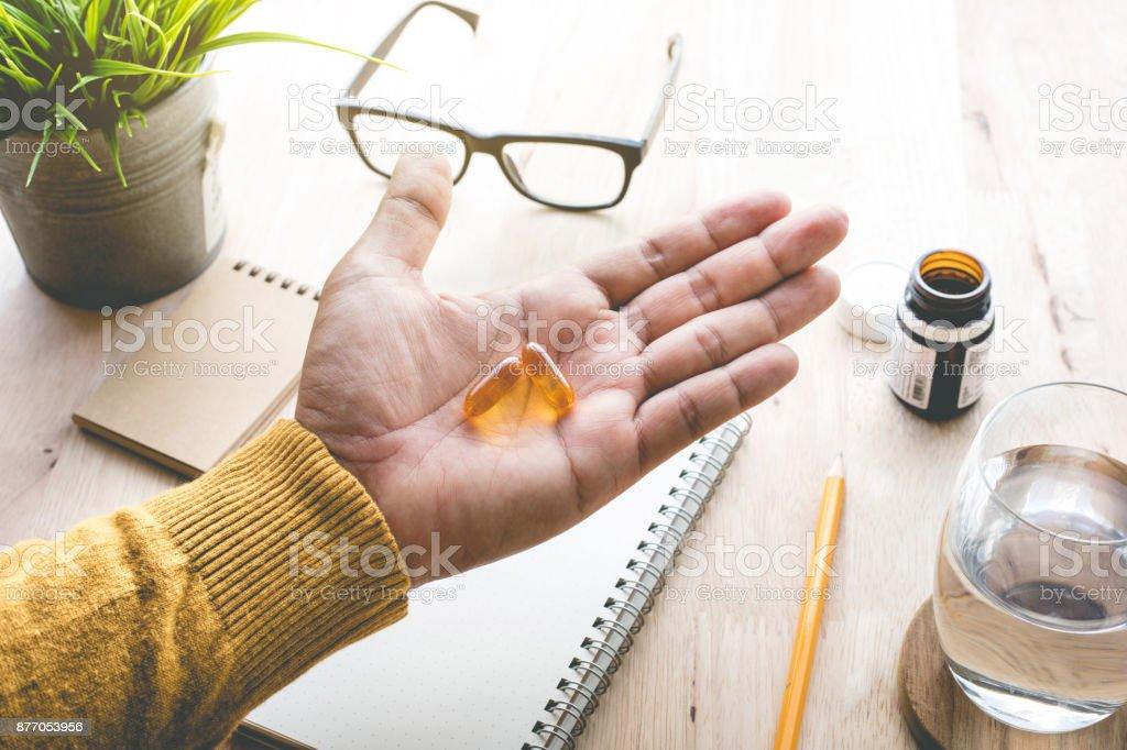 Macho comendo a remédio, comprimido (vitamina) no trabalho de manhã. - foto de acervo