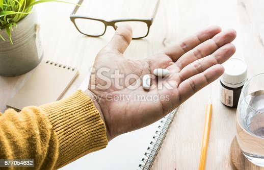 istock Male eating medicine,pill (vitamin) on work in morning. 877054632