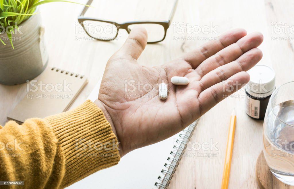 Male eating medicine,pill (vitamin) on work in morning. stock photo