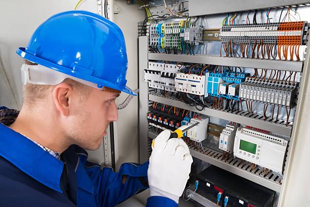 male electrician examining fusebox - electricista fotografías e imágenes de stock