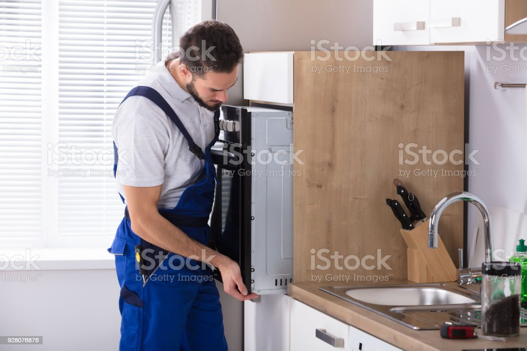 Male Electrician Fixing Oven stock photo