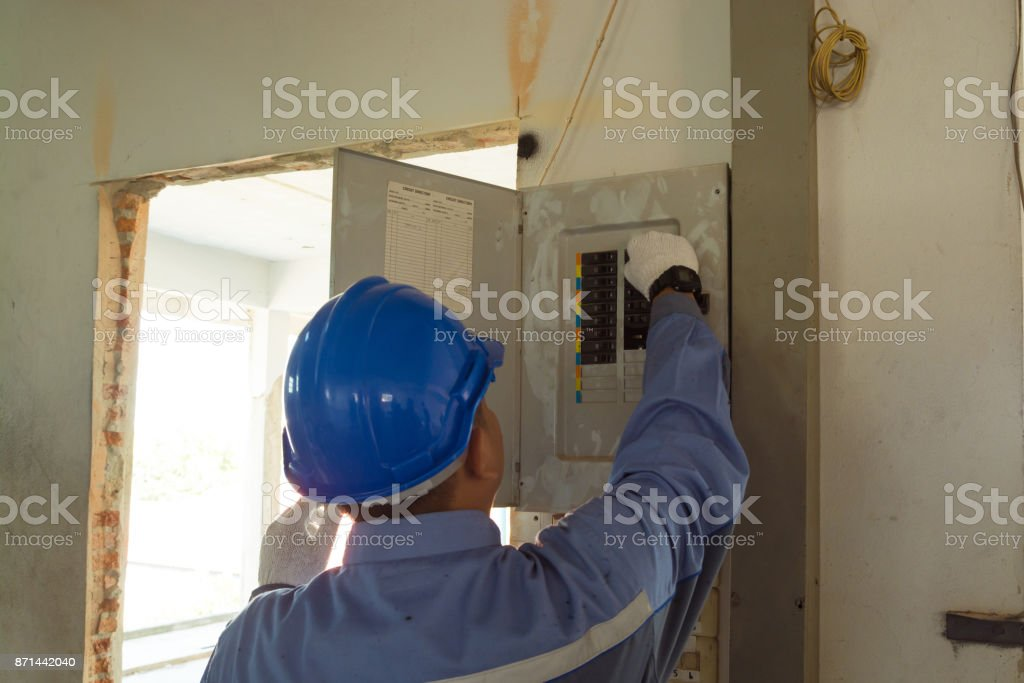 Male Electrician or Engineer check or Inspect Electrical System circuit Breaker stock photo