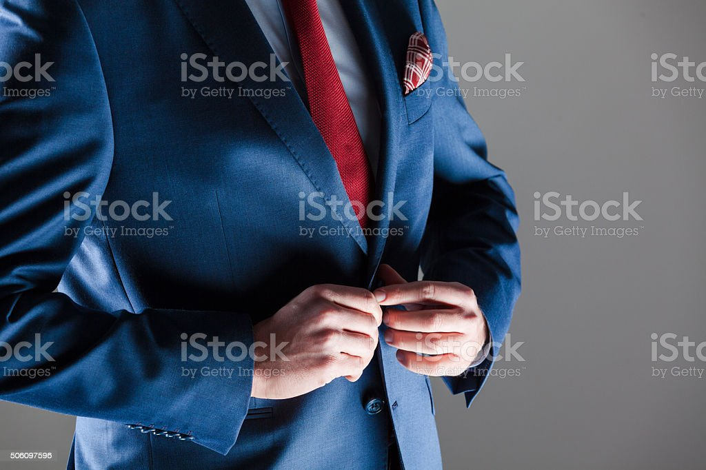 Male elegance, businessman wearing navy blue suit Close up of elegant busienssman wearing navy blue jacket, red tie and pocket square. Unrecognizable person, part of.  Adult Stock Photo