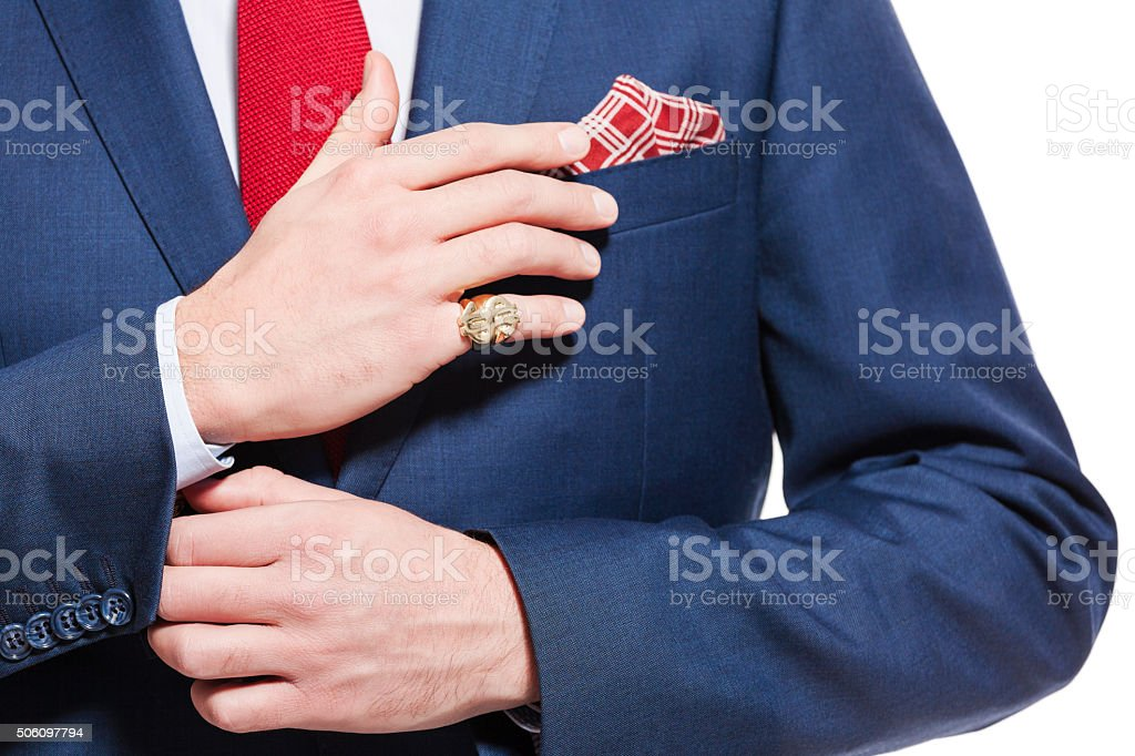 Male elegance, businessman wearing navy blue suit Elegant busienssman wearing navy blue jacket, red tie and pocket square. Unrecognizable person, part of, close up of hands. Adult Stock Photo