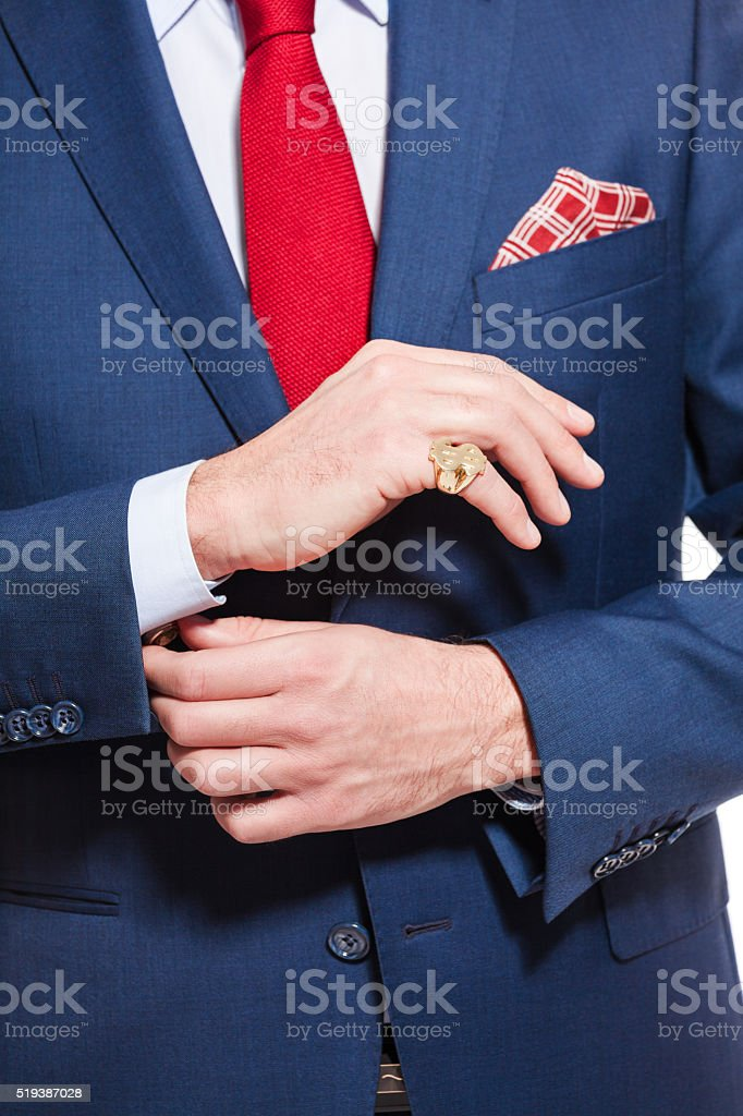 Male elegance, businessman wearing navy blue suit Elegant busienssman wearing navy blue jacket, red tie and pocket square. Unrecognizable person, part of, close up of torso and hands. Adult Stock Photo