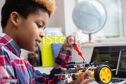 Male Elementary School Pupil Building Robot Car In Science Lesson