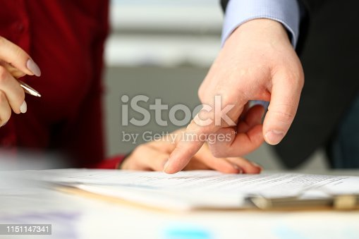 istock Male employee boss arm showing with finger something in document 1151147341