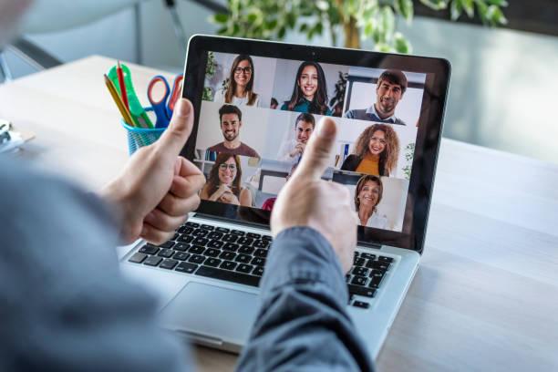 Männliche Mitarbeiter, die eine gestikulierende Zustimmung mit Daumendrücken, während sprechen auf Videoanruf mit verschiedenen Kollegen auf Online-Briefing mit Laptop zu Hause. – Foto