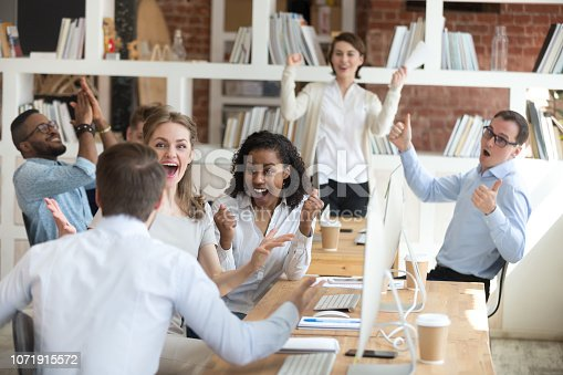 istock Male employee share good news with excited diverse colleagues 1071915572
