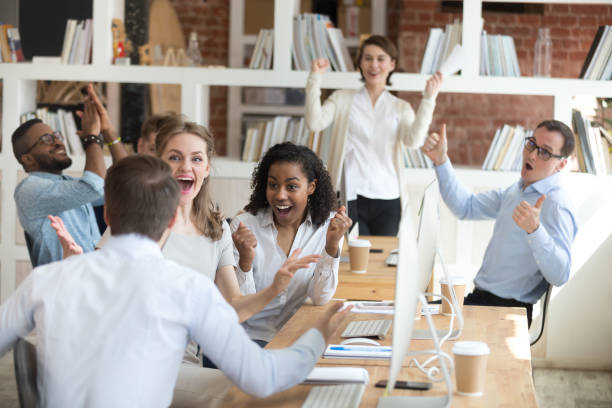 Male employee share good news with excited diverse colleagues Male worker share good news with multiracial colleagues in shared workplace, diverse employees scream with happiness excited with corporate success or goal achievement, team celebrating win achievement stock pictures, royalty-free photos & images