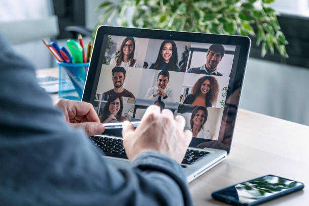 Male employee speaking on video call with diverse colleagues on online briefing with laptop at home. Back view of male employee speaking on video call with diverse colleagues on online briefing with laptop at home. video call stock pictures, royalty-free photos & images