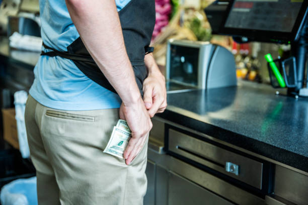 a male employee stealing cash at the checkout in a store - thief stock photos and pictures