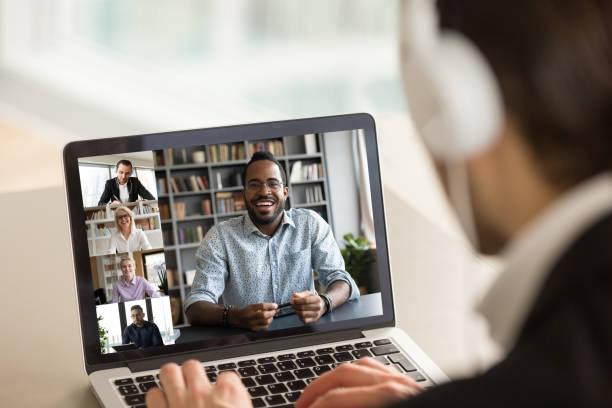 Männliche Mitarbeiter sprechen im Videoanruf mit diversen Kollegen – Foto