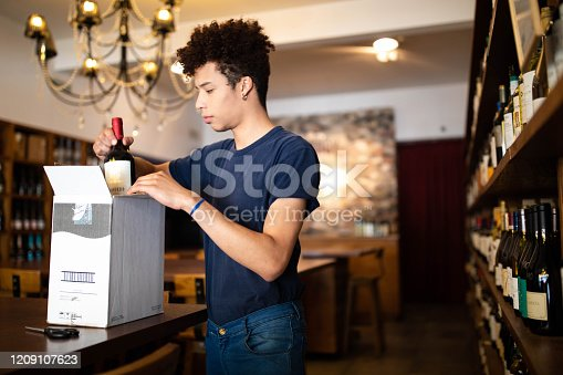 Young man at store counter taking out wine bottle from a cardboard box. Male employee working at wine store.
