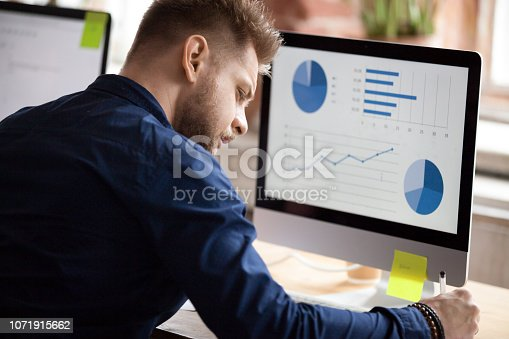 istock Male employee working with graphs on pc in office 1071915662