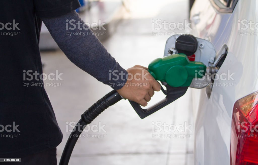 male employees controlled the fuel pump  with Fuel nozzles adding gasoline fuel in car at a pump gas station stock photo