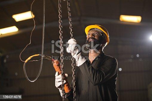 1047558948 istock photo Male engineer adjusting chain hoist at industry 1264314076