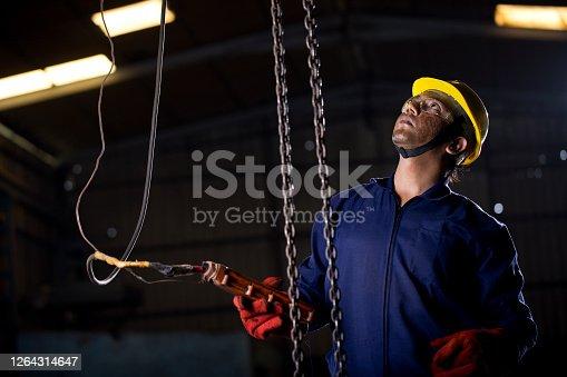 1047558948 istock photo Male engineer adjusting chain hoist at industry 1264314647