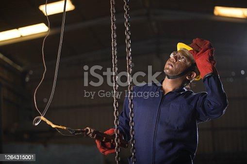 1047558948 istock photo Male engineer adjusting chain hoist at industry 1264315001