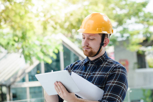 Male engineer at a construction site with a tablet computer Male engineer at a construction site with a tablet computer project manager stock pictures, royalty-free photos & images