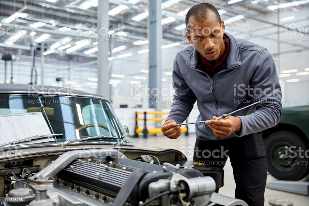Male engineer checking oil with dipstick by car stock photo