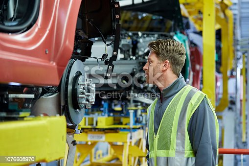 941796726istockphoto Male engineer checking vehicle at car plant 1076608970