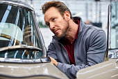 Mature male engineer examining vintage car in industry. Technologist is crouching by motorvehicle in industry. He is working in automobile showroom.