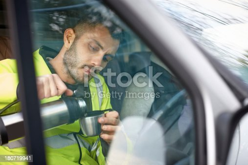 istock Male engineer having a cup of coffee in his car 180719941