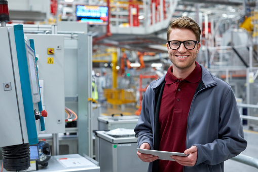 Portrait of mid adult engineer holding digital tablet by control panel at automobile industry. Confident professional is wearing uniform. Male is standing at car plant.