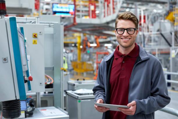 mannelijke ingenieur houden van tablet pc op autofabriek - robot engineer stockfoto's en -beelden