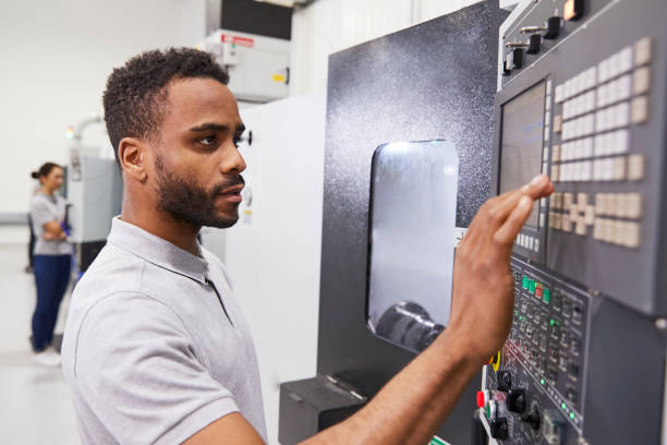 Male Engineer Operating CNC Machinery In Factory stock photo