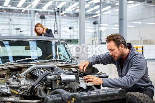 941796726istockphoto Male engineer repairing vintage car in industry 916868256